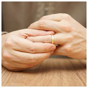 person facing divorce removing wedding band